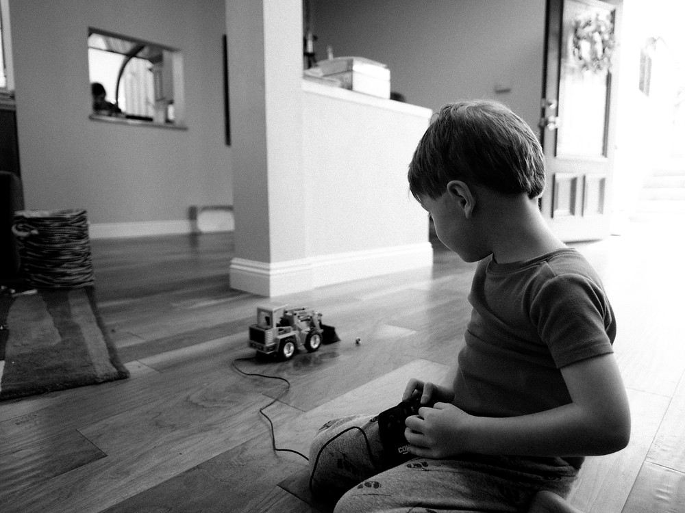 Young boy playing with a toy truck and looking away from camera