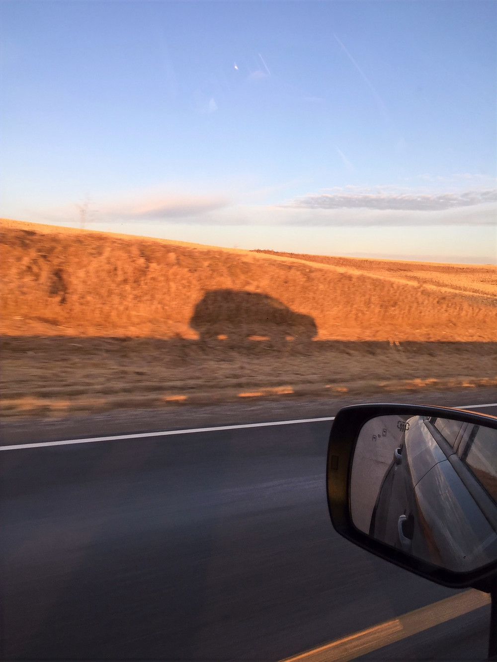 Picture of the shadow of my car as I drive along the highway from Iowa to Vermont