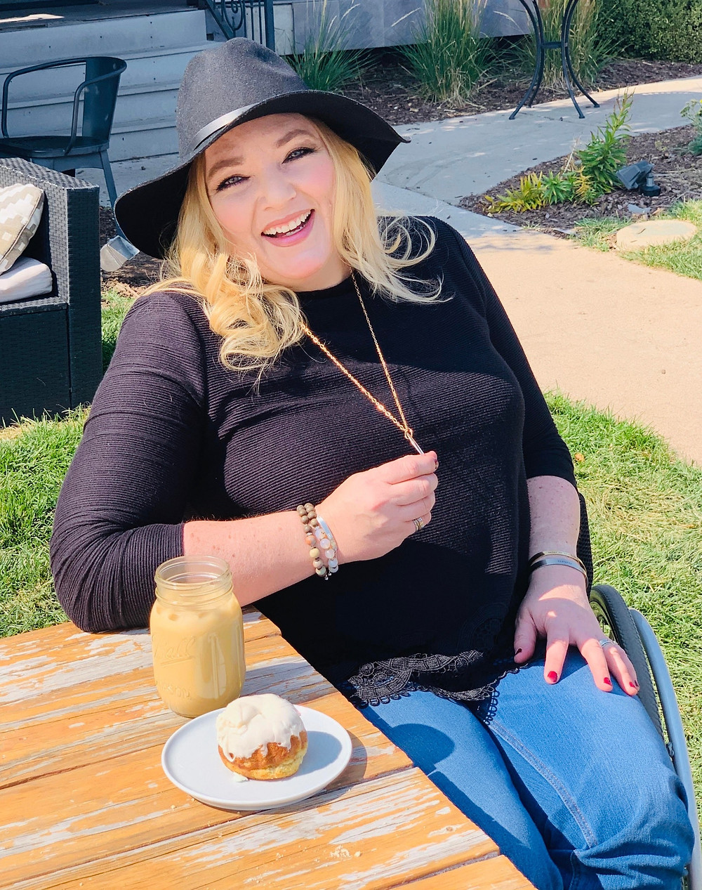 Kate is seated outside at a wood table, she is having an iced coffee and donut. She is wearing black sweater, jeans, and black suede hat. She is also wearing our fidget necklace and she is fidgeting with it.