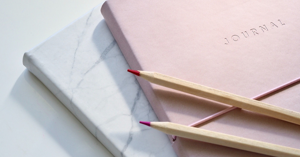 Graphic- pink and grey journals with red colored pencils