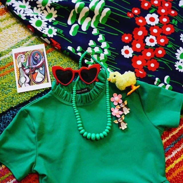 Flat lay photo of colourful items. I.E. green crop top, green beaded necklace, red heart sunglasses, etc.