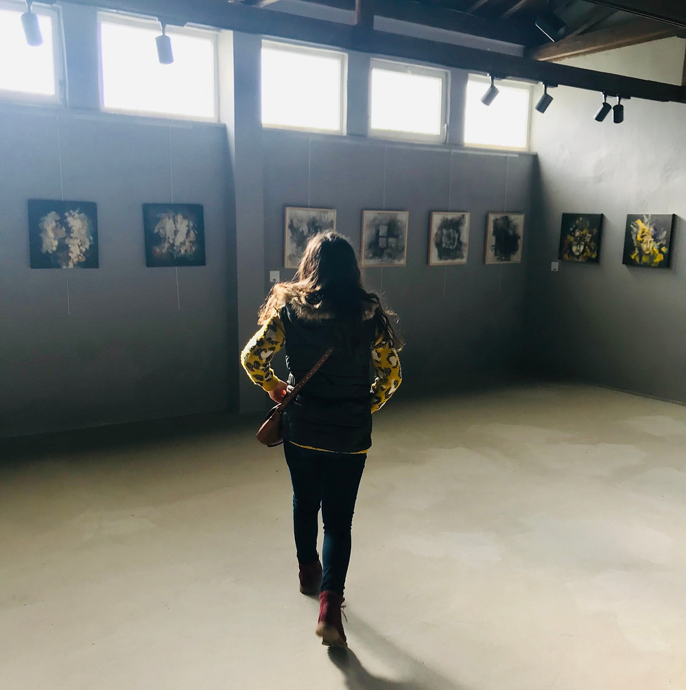 Woman in an art gallery in Turkey, contemplating creativity and personal growth