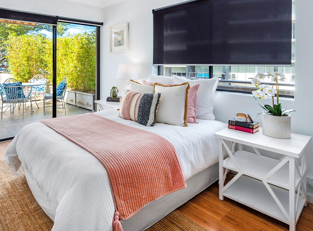 Light and bright bedroom setting with Hampton theme and outdoor setting in background