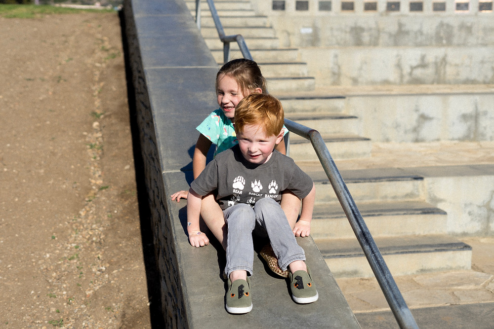 Young boy and girl going down a slide together