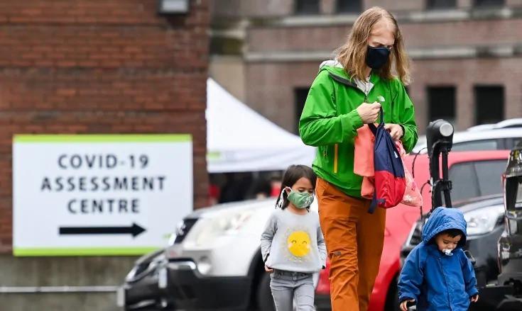Una familia hace fila para hacerse la prueba de COVID-19 en un centro de pruebas de Toronto.