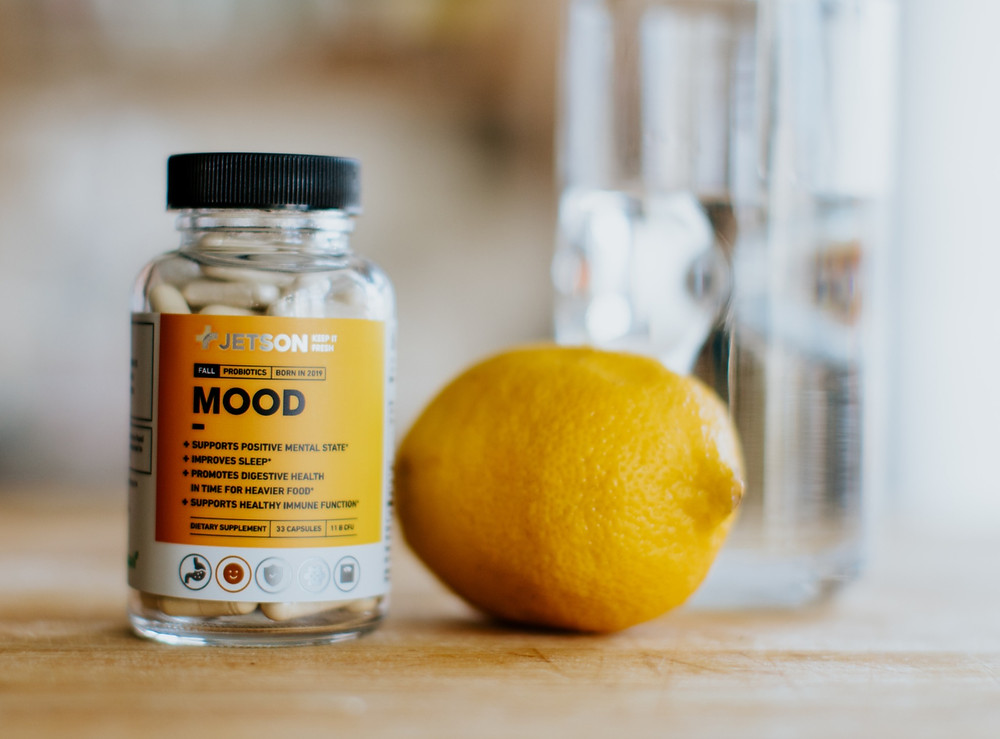 Bottle of pills sitting next to lemon in front of glass of water