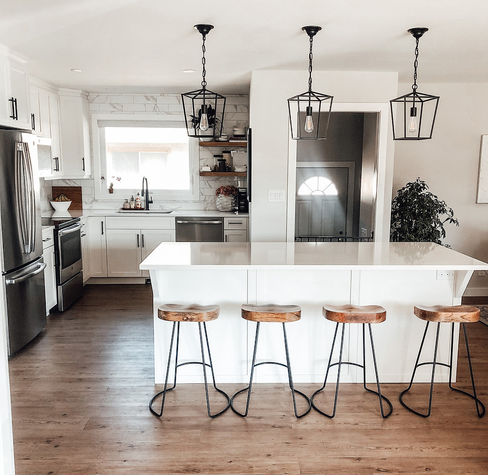 white kitchen and wooden stools