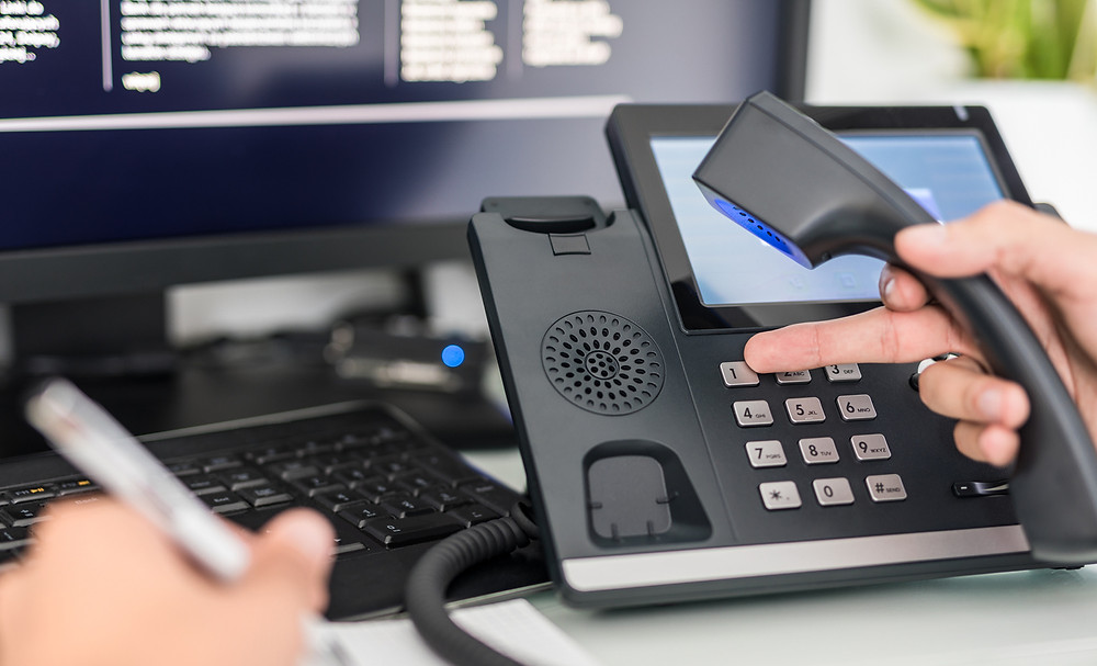 Person using telephone sitting next to desktop computer
