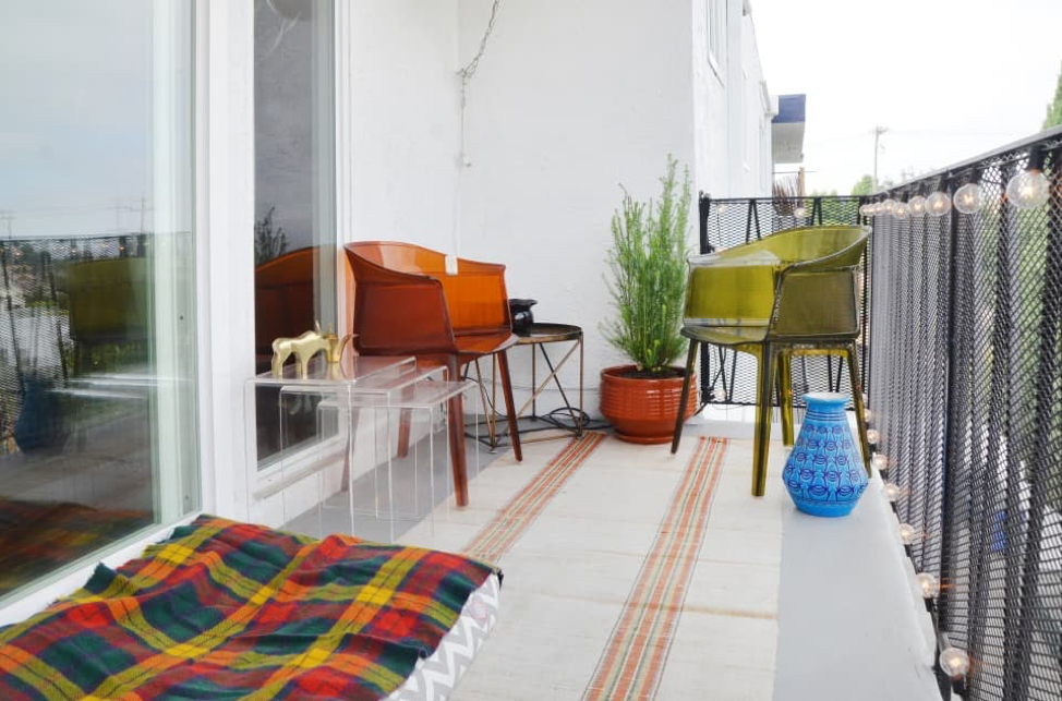 Want to be the talk of the town for your trending ideas to decorate a small balcony? Then, this vibrant, colorful, and eclectic mix of outdoor styles is what you should aim for. Created with these magnificent lucite chairs, this warm color pallet creates nostalgia of the '70s.  However, this chic rug, planters, and outstanding chiminea provide a precise Mediterranean vibe.
