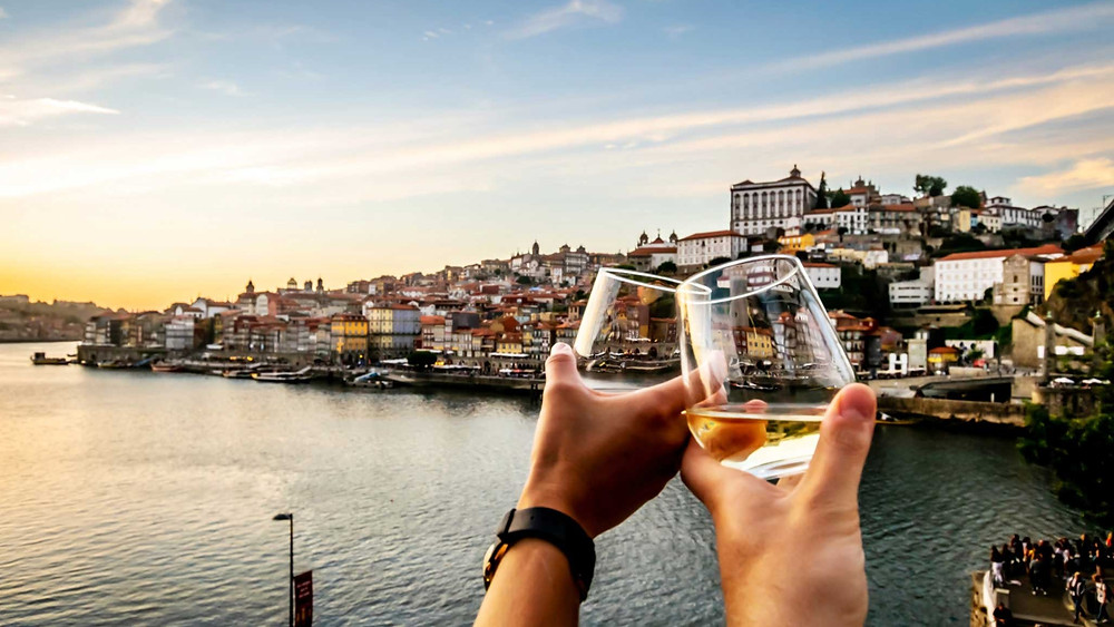 Glasses of white wine and the Douro river in the city of Porto