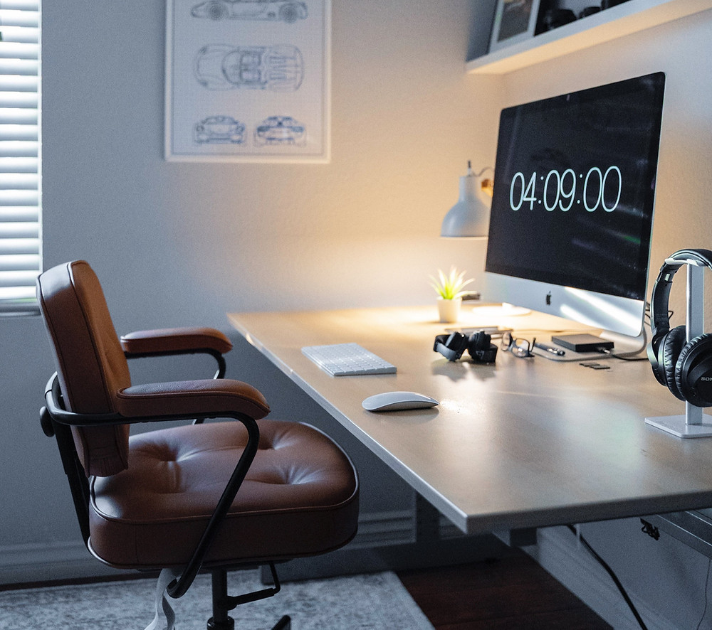A working from home set up. With a computer on a desk, wireless headphones, mouse and keyboard alongside a office chair.
