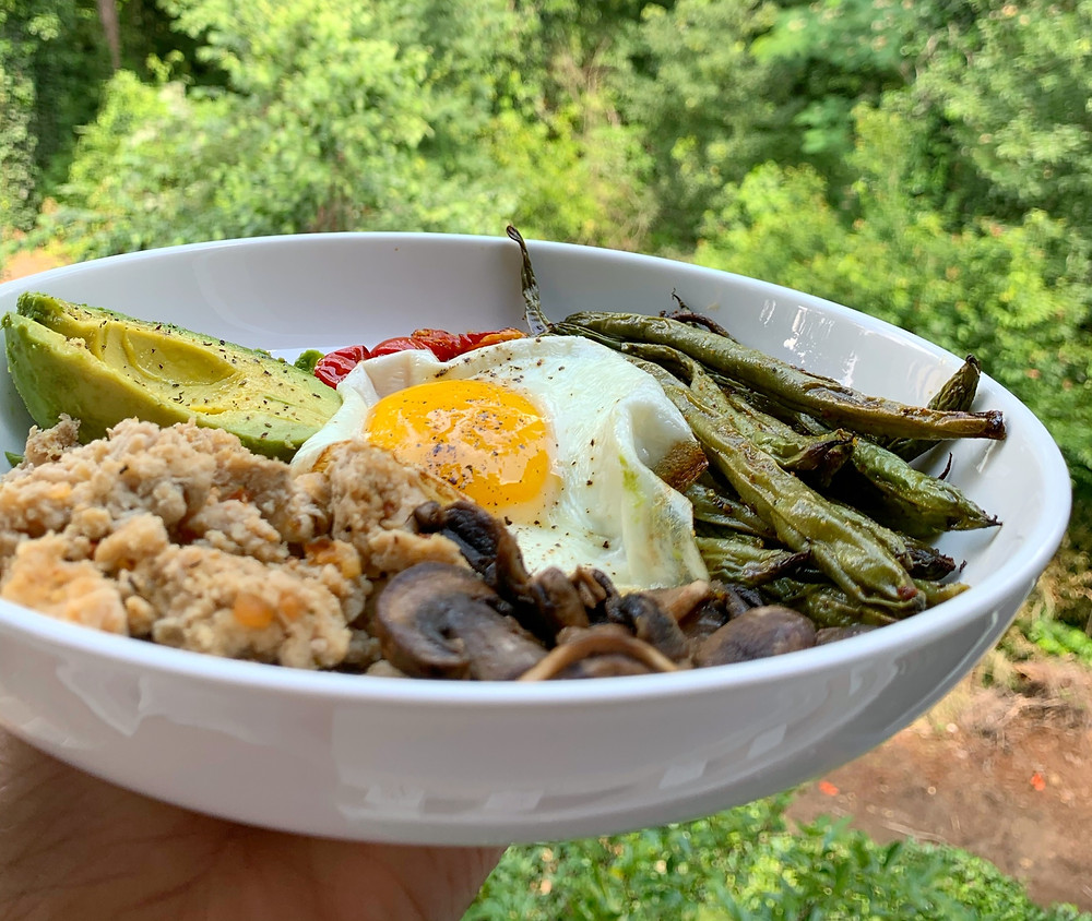 surface level shot of burger bowl with ground chicken, avocado, mushrooms, tomatoes, green beans, and fried egg