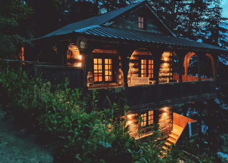 a lighted wood and stone house amidst many trees | North Homestay in Naggar