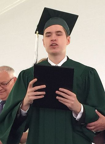 Image of Franklin Nichols, wearing his green graduation cap and gown, posing with his diploma.