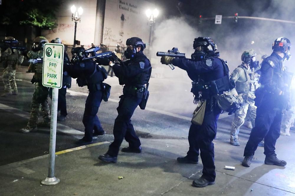 Police pointing guns at protestors.