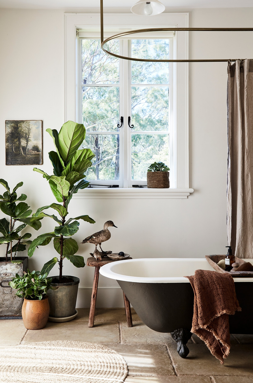 Light filled vintage style bathroom with a vintage clawfoot tub painted black and stone floors