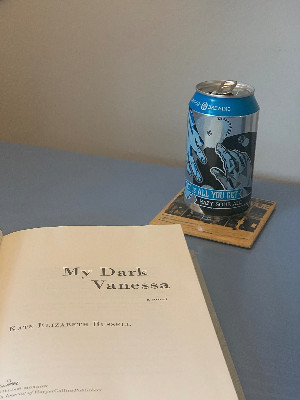 Open copy of My Dark Vanessa on a table with an open can of beer next to it.