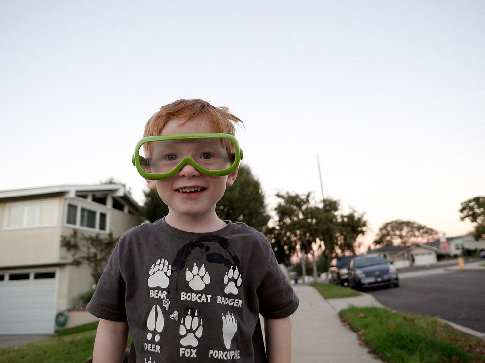 Young boy with science goggles on smiling at the camera