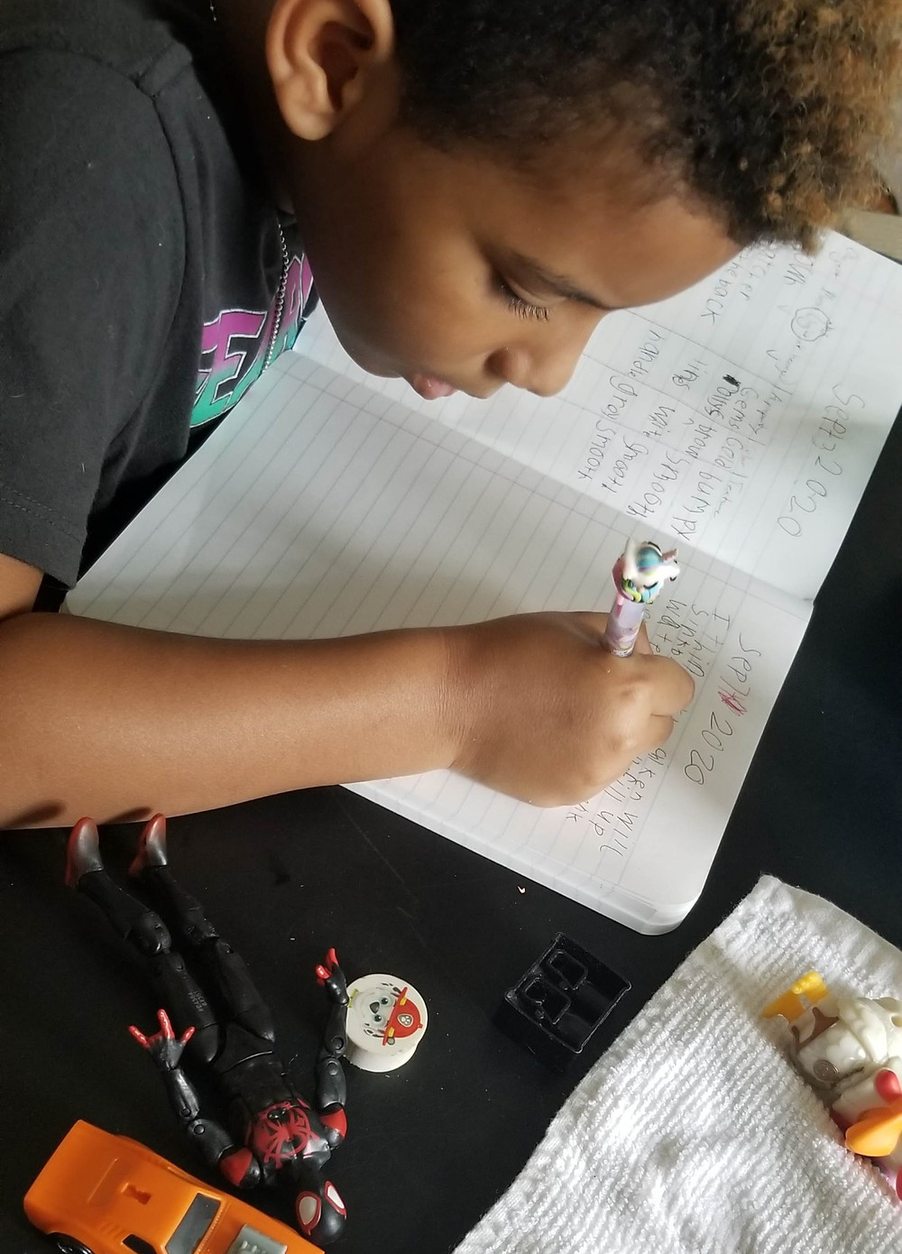 """Blaze writing his predictions and findings in his science journal as he conducts a """"sink or float"""" experiment."""