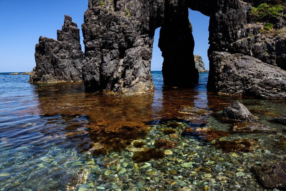 透明な海と奇岩のアーチ / Rocks and arches of unusual shape on clear sea