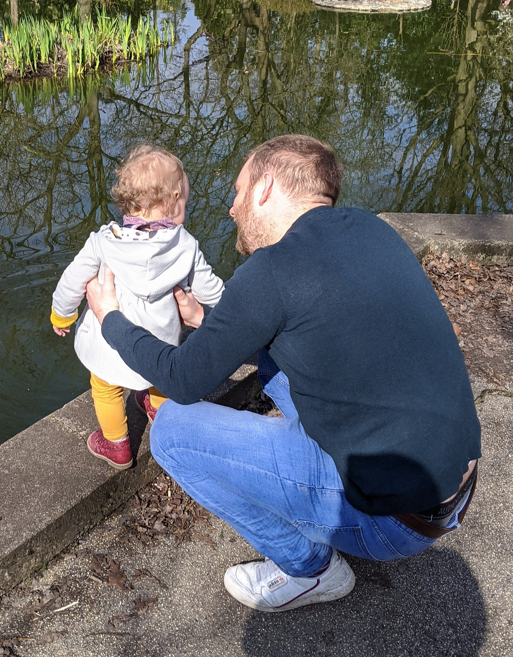 Dad and his baby girl looking for tadpoles in a pond