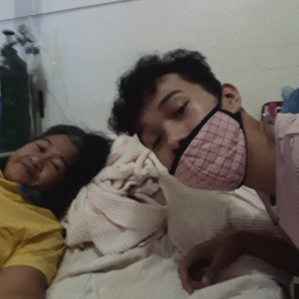 A boy wearing a pink mask in a picture with his mother lying on a bed