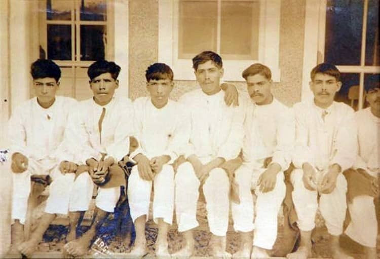 Seven men in white clothing sit next to each other in an old sepia-toned photograph.