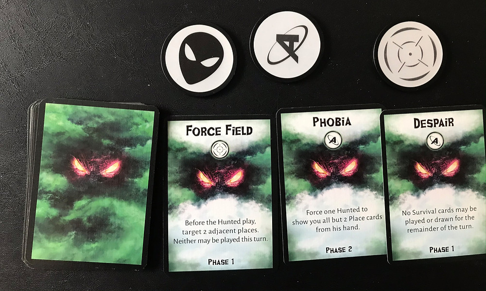 The little icon under the name indicates that playing the card grants the Creature an extra token that round. The Force Field lets the Creature play the Target marker, which has an effect based on the rules text. The Phobia and Despair hunt cards let the Creature use the Artemia marker, even if the Hunted haven't reached the Artemia section of the victory track yet.