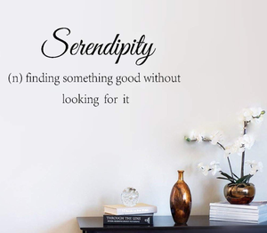 wall-decal-with-definition-of-the-word-Serendipity-on-the-wall-with-table-under-it-with-books-vase-and-orchid-on-it