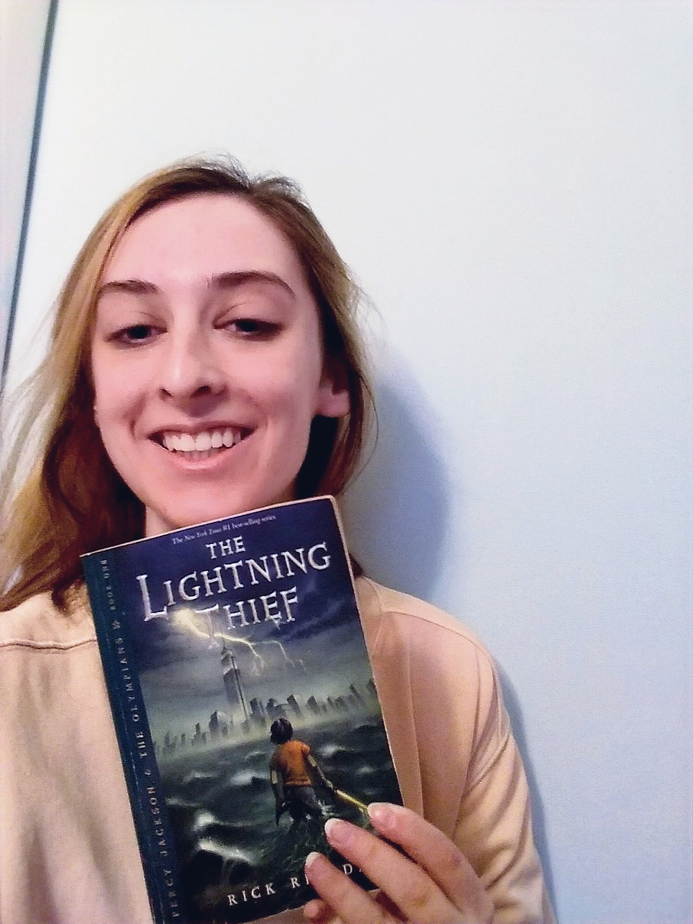 A photo of me holding my copy of the Lightning Thief.