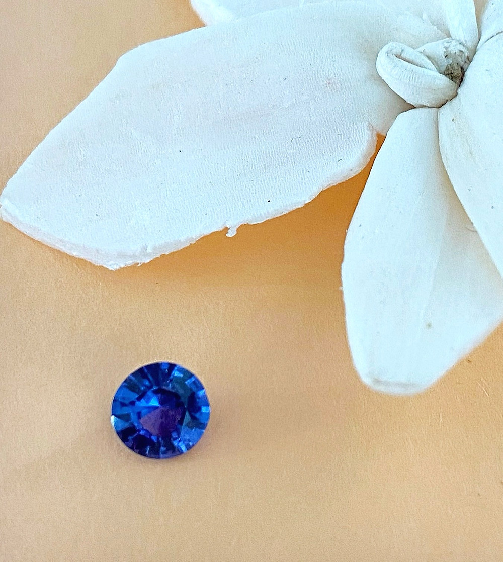 loose round cut purple sapphire on a peach background next to white flower