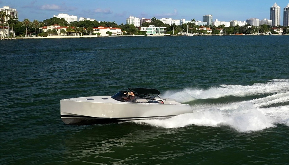 Couple driving a gray and black cigarette boat on Miami's Biscayne Bay