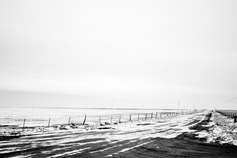 Snow covered dirt road in Yoder, CO with wind mills looming in the distance