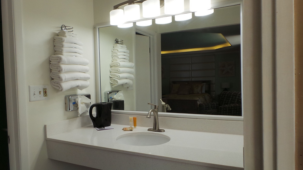 Vanity with sink, tissue holder, towel rack, shampoo, conditioner, light bar