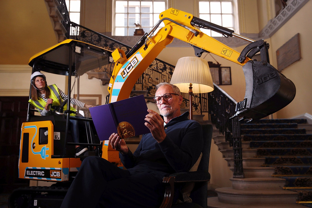Man reading a brochure in front of 19C-1E excavator in the bad