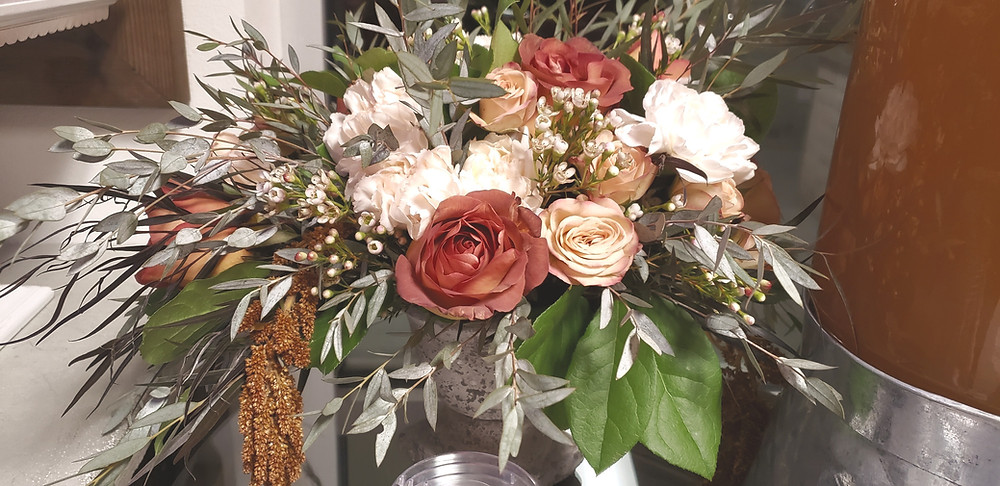 Flower arrangement with roses, amaranthus and eucalyptus.
