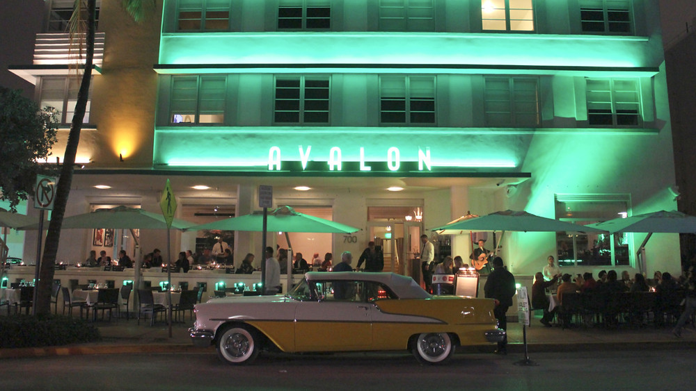 South Beach Miami classic car parked in front of neon light hotel at night