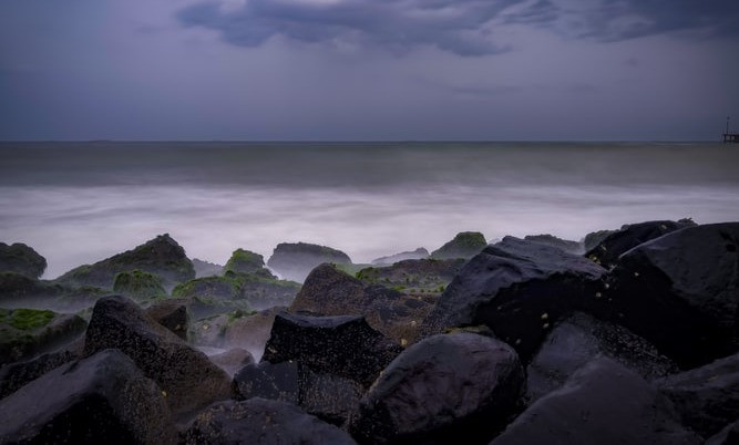 Rocky shore under cloudy sky and beach