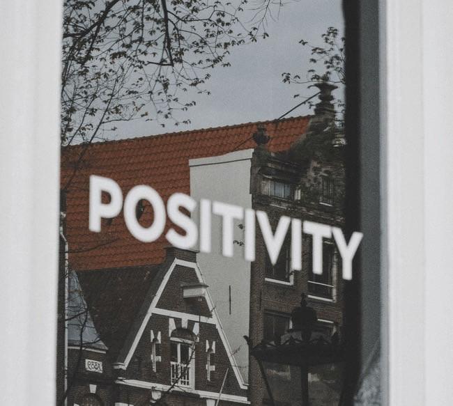 """Window with """"positivity"""" written on it."""