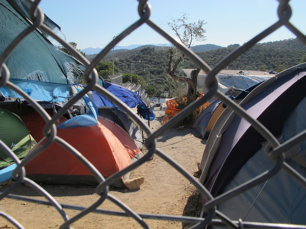 A photo through a chain link fence of tents in the Moria camp.