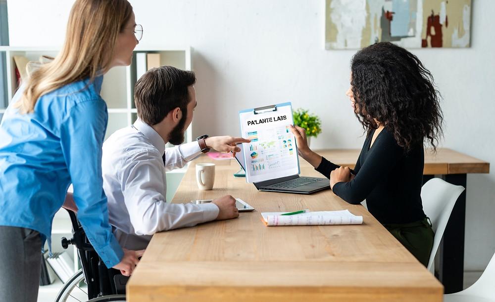 En la imagen se ven dos ejecutivas y un ejecutivo viendo una tabla de resultados positivos con el título Palante Labs.