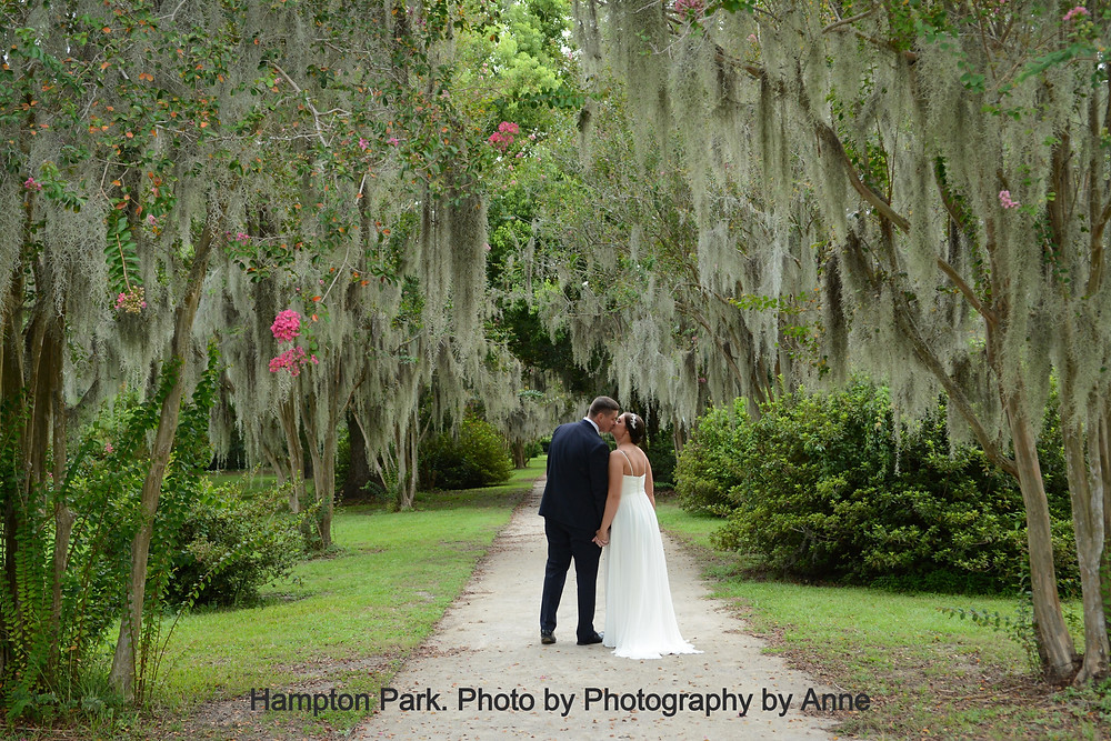 Bride and Groom kiss along a path lined in crepe myrtle covered in spanish moss in Hampton Park