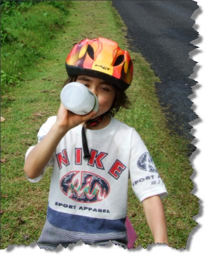 Boy drinking water while riding a bike in Samoa
