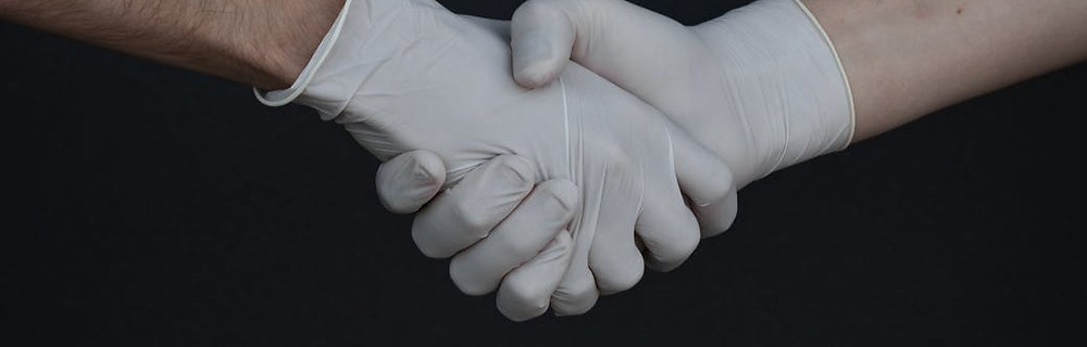 Two hands shaking each other wearing white gloves