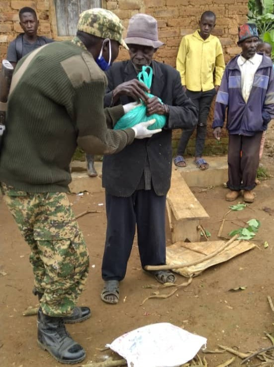 A member of the Ugandan army helps the Eco Brixs Coronavirus Relief Programme by handing out food to a 80 year old man