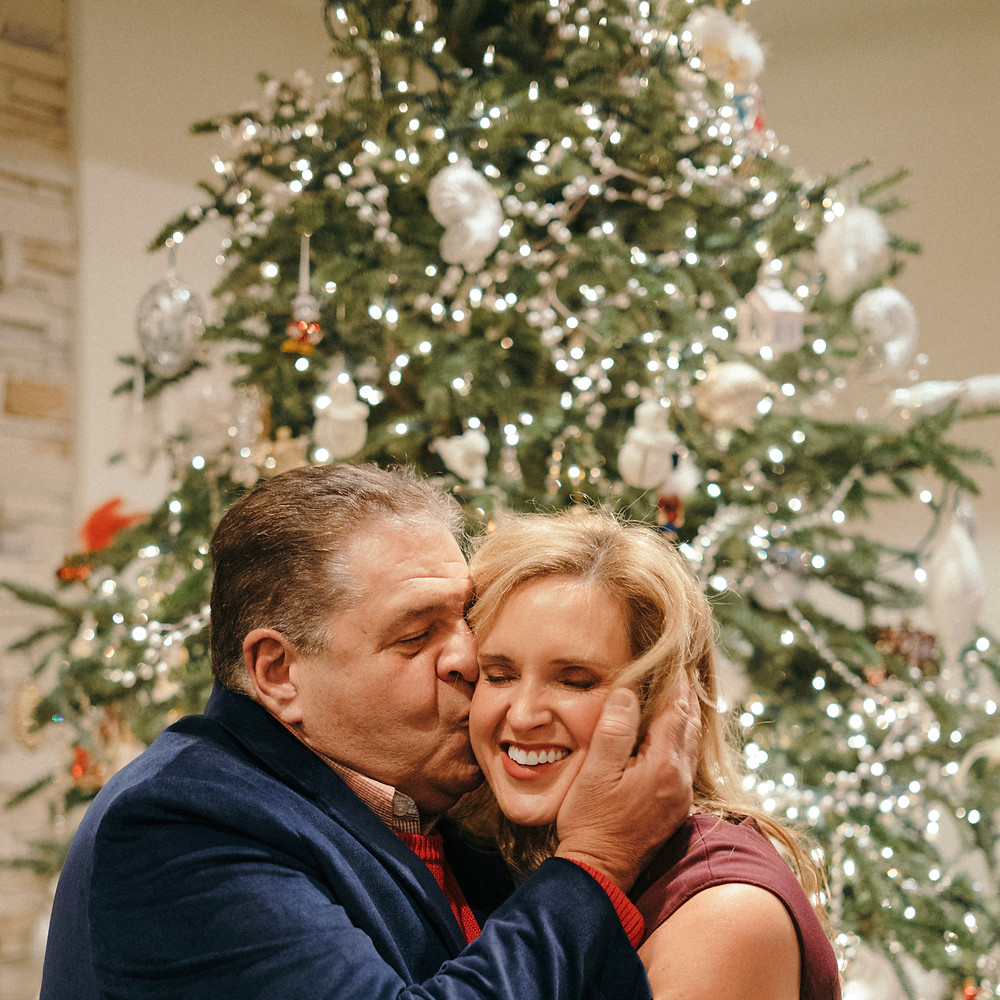 Husband and wife kissing in front of Christmas tree