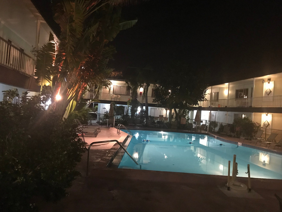 Photo of pool and courtyard under lights in the evening
