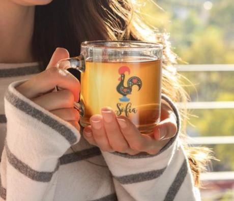 A girl holds a glass Galo de Barcelos coffee mug