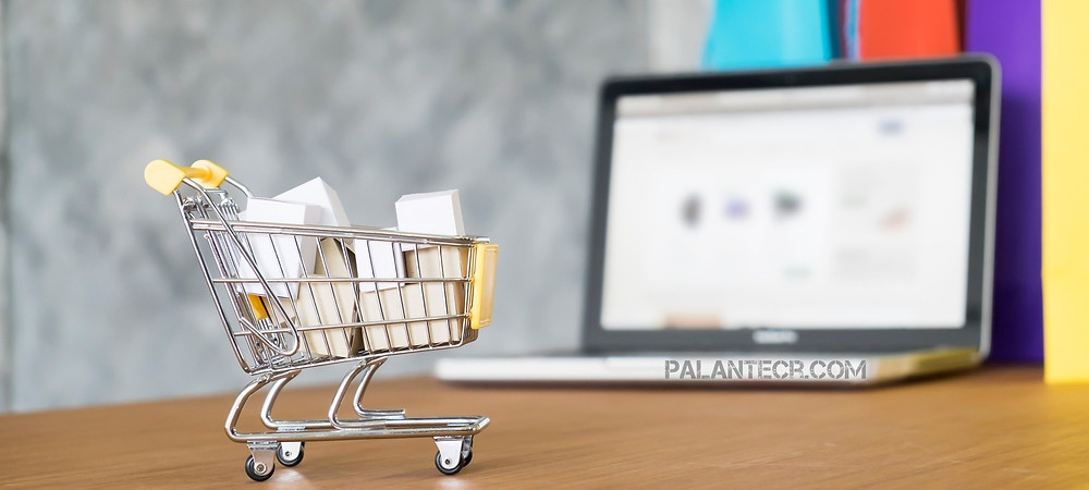En la imagen se ve un carrito de compras miniatura lleno de cajas con unca computadora portatil a lo lejos y en el borde frontal de la computadora el texto: [PalanteCR.com]