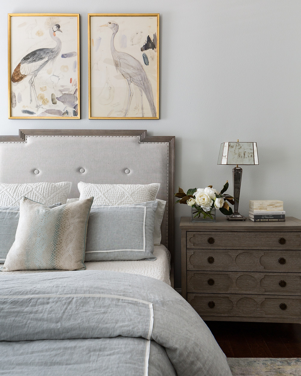 Guest bedroom in Cinco Ranch, Katy TX with wood-framed upholstered bed. Linen bedding and bird art